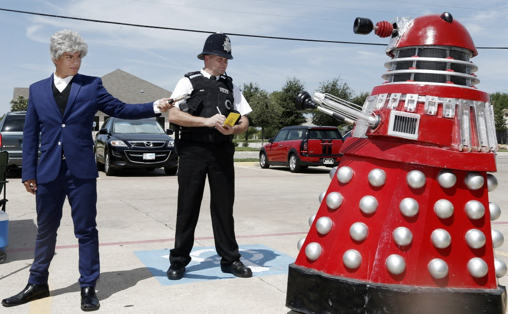Nicholas Woody, 14, left, dressed as the 12th Doctor, and Glenn Wilson, dressed as a British police officer, face off against a Dalek, an extraterrestrial race of cyborgs from the Doctor Who series, during a Doctor Who fan meet up at the British Emporium in Grapevine, Sunday, August 24, 2014.