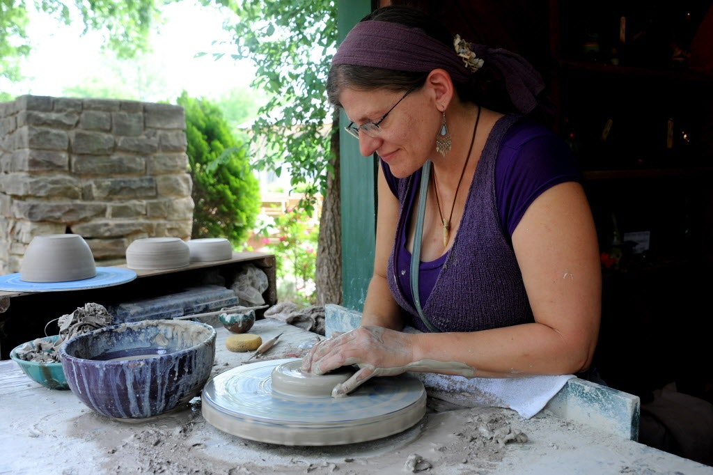 Pottery apprentice, Eva Lauenz, creates ceramic bowls at Scarborough Renaissance Festival in Waxahachie, TX on April 27, 2014.
